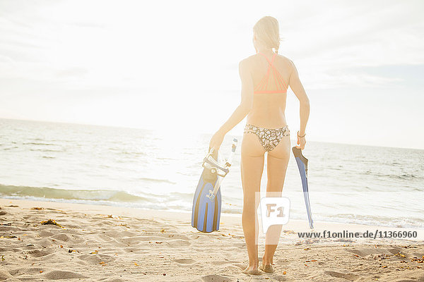 Rear view of woman on beach carrying swimming flippers