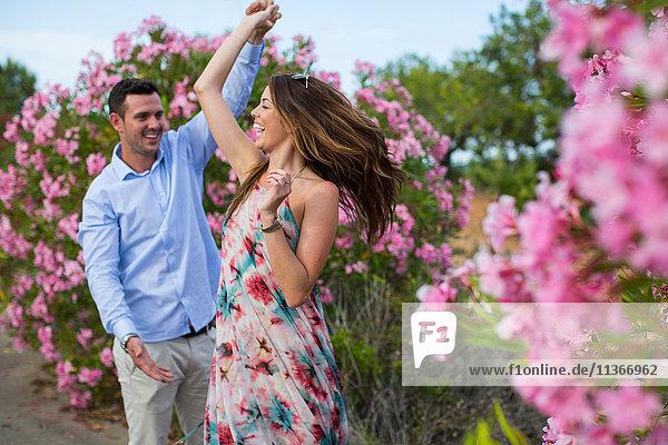 Romantisches Paar tanzt und wirbelt vor Blüten  Mallorca  Spanien