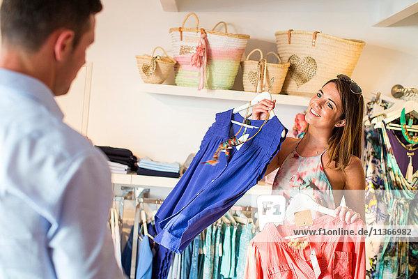 Junge Frau  die ihren Freund zum Kleiderkauf in einer Boutique verführt  Mallorca  Spanien
