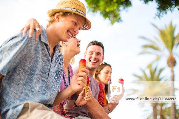 Vier erwachsene Freunde  die lachen und Eiswaffeln essen  Mallorca  Spanien