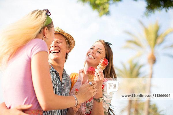Drei erwachsene Freunde lachen und essen Eistüten  Mallorca  Spanien