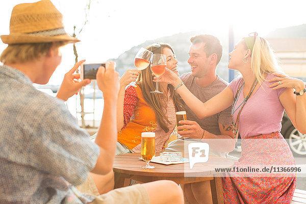 Junger Mann fotografiert erwachsene Freunde im Restaurant am Wasser  Mallorca  Spanien
