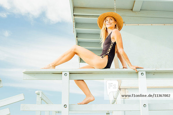 Woman wearing swimsuit on lifeguard tower looking away