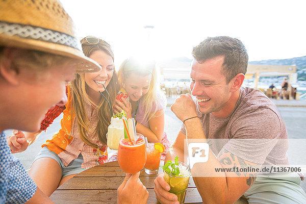 Zwei erwachsene Paare lachen bei Cocktails in einem Restaurant am Wasser  Mallorca  Spanien
