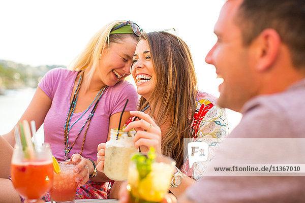 Drei erwachsene Freunde lachen bei Cocktails im Hafenrestaurant  Mallorca  Spanien