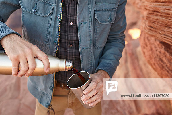 Man pouring hot drink from drinking flask  mid section  Page  Arizona  USA