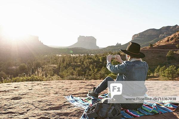Frau sitzt auf einer Decke in der Wüste und fotografiert mit einem Smartphone  Sedona  Arizona  USA