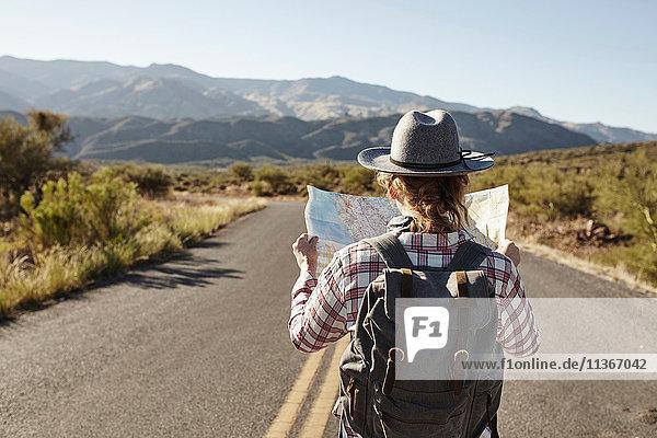 Frau steht auf einer Wüstenstraße und schaut auf die Karte  Sedona  Arizona  USA