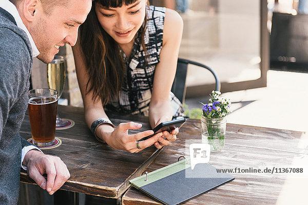 Junges Paar sitzt vor einer Bar und schaut auf ein Smartphone
