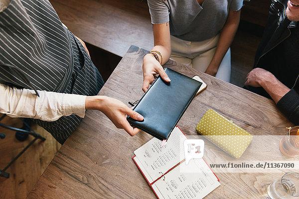 Restaurantangestellter überreicht Gesetzentwurf für ein junges Paar  Mittelteil