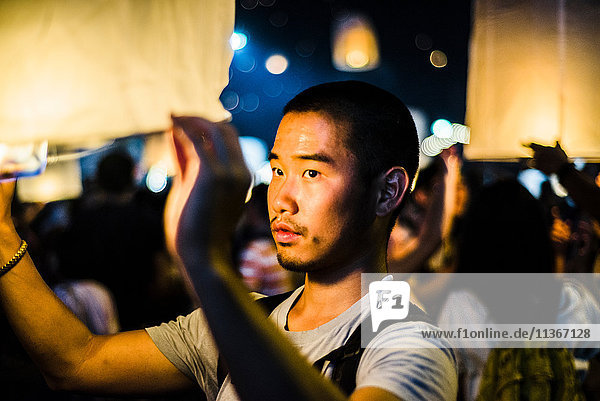 Young man holding lit paper lantern waiting to release at Loy Krathong Paper Lantern Festival in Chiang Mai  Thailand