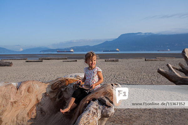 Little girl playing on wood sculpture on beach  Vancouver  British Columbia  Canada