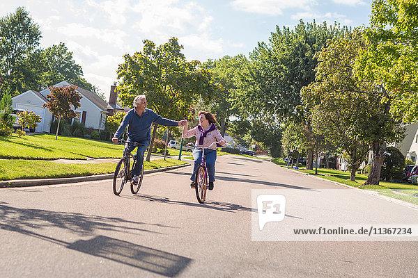 Romantisches älteres Ehepaar hält sich an der Hand und fährt mit dem Fahrrad die Vorstadtstraße entlang