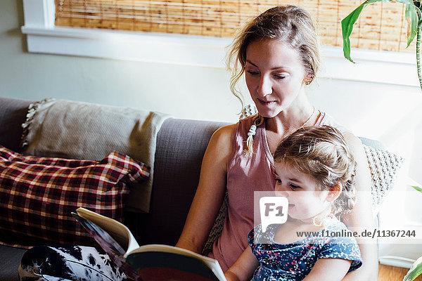 Frau auf Sofa mit Kleinkind Tochter liest Märchenbuch
