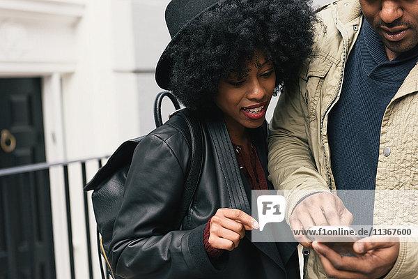 Ehepaar auf der Straße betrachtet Smartphone