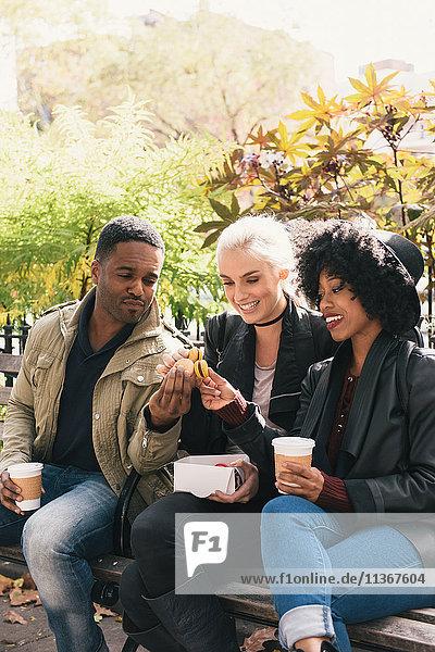 Freunde sitzen nebeneinander auf der Parkbank