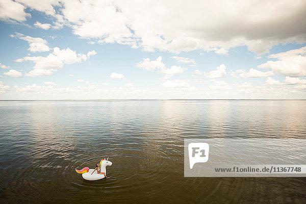 Weitwinkel-Distanzansicht einer jungen Frau  die auf einem aufblasbaren Einhorn im Meer sitzt  Santa Rosa Beach  Florida  USA