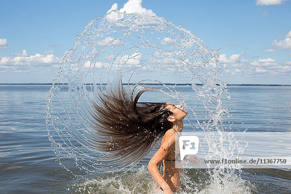 Young woman splashing and throwing back long hair from sea  Santa Rosa Beach  Florida  USA