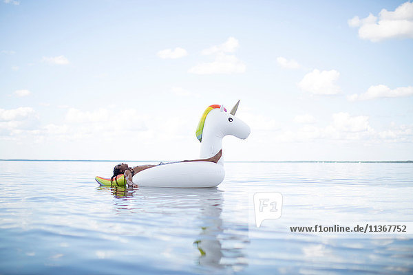 Young man lying back on inflatable unicorn in sea  Santa Rosa Beach  Florida  USA