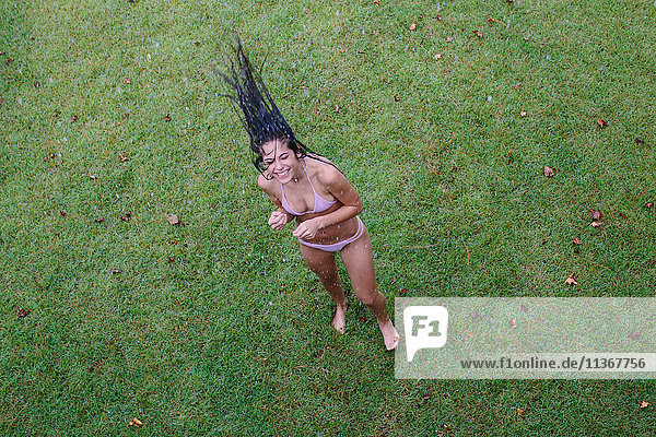 Overhead portrait of young woman throwing back long wet hair on lawn  Santa Rosa Beach  Florida  USA
