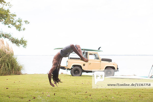 Young man doing backflip on coastal grass  Santa Rosa Beach  Florida  USA