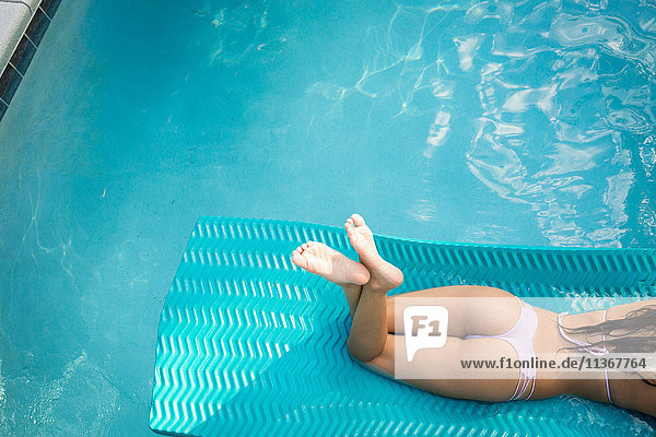 High angle neck down view of young woman sunbathing in swimming pool  Santa Rosa Beach  Florida  USA