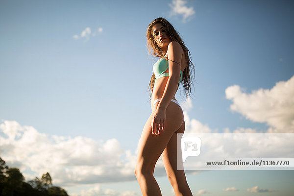 Low angle portrait of young woman with long hair in bikini at coast  Santa Rosa Beach  Florida  USA