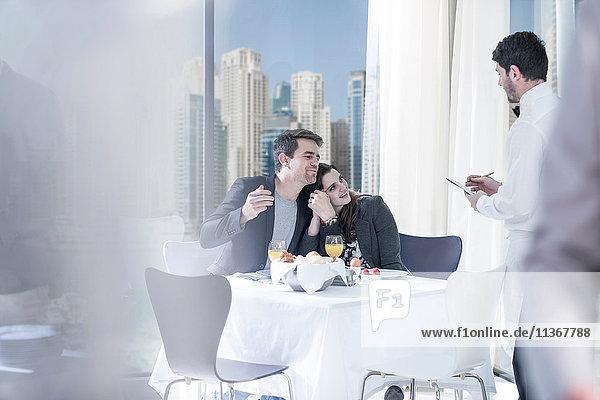 Romantisches junges Paar bestellt Frühstück im Hotelrestaurant