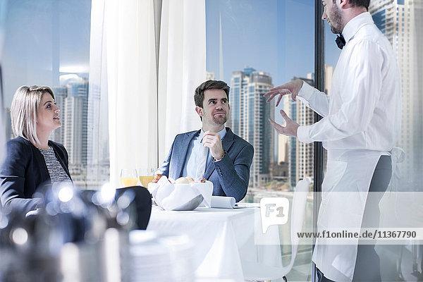 Geschäftsmann und -frau beim Frühstück im Hotelrestaurant