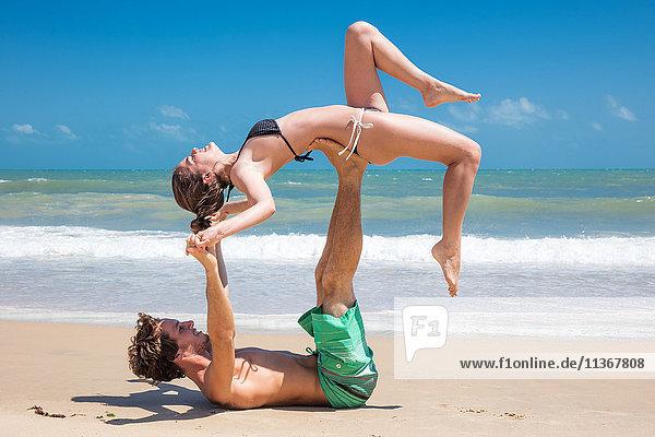 Junger Mann balanciert mit seiner Freundin über ihm am Strand  Taiba  Ceara  Brasilien