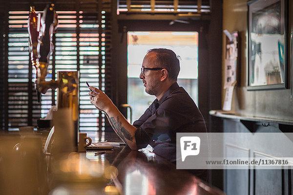 Barkeeper liest Smartphone-Texte am Tresen einer Gaststätte