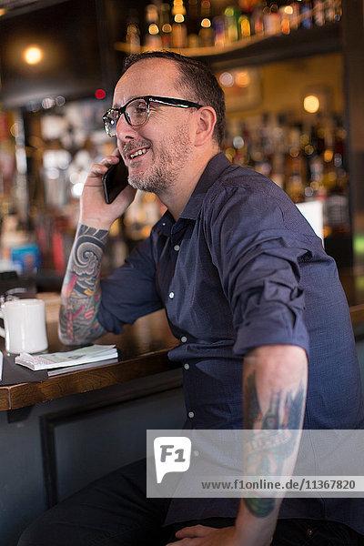 Barmann spricht mit Smartphone am Tresen einer Gaststätte