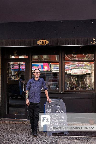 Porträt eines Barmanns  der sich vor dem Fenster einer Kneipe an ein Happy-Hour-Brett lehnt  Brooklyn  New York  USA