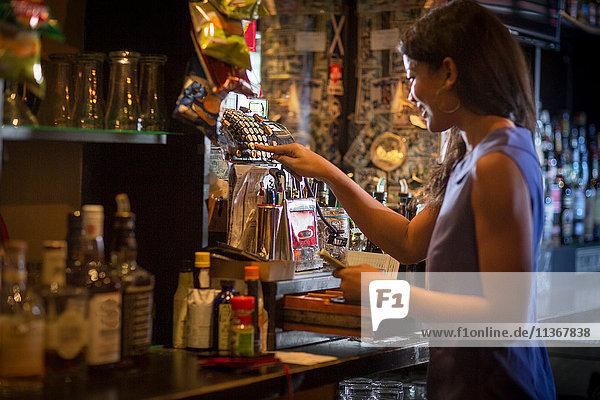 Barfrau benutzt Registrierkasse in einer Gaststätte