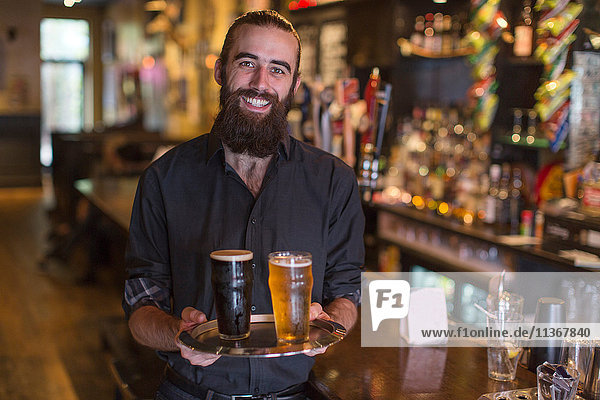 Porträt eines jungen männlichen Barkeepers mit einem Tablett mit Bier in einer Gaststätte