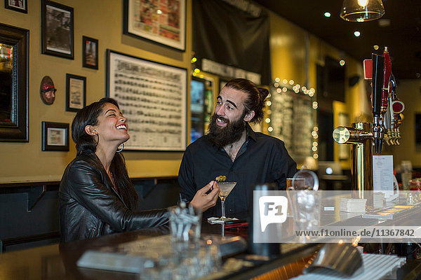 Junges Paar am Tisch lachend in der Kneipe