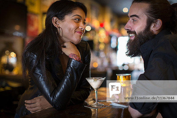 Romantic young couple with cocktail and beer in public house