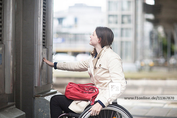 Young woman using wheelchair pressing control for city elevator