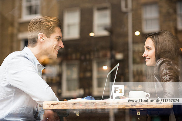 Young businessman and woman with laptop talking in cafe