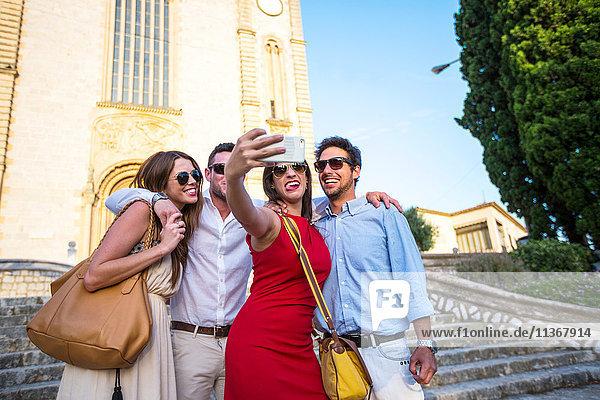 Zwei Touristenpaare beim Selfie vor der Kirche  Calvia  Mallorca  Spanien