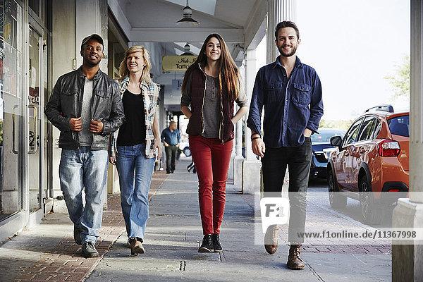 Two young men and two young women walking along a sidewalk  smiling into shot.