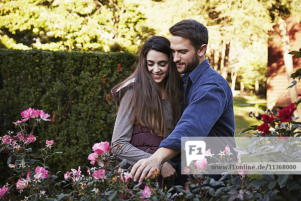 A young man and woman standing in a garden  looking at a flowering plant together.