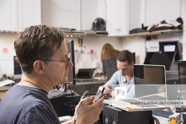 Drei Personen  die in einem Technologielabor arbeiten  mit einem Mann im Vordergrund  der auf ein Mobiltelefon schaut.
