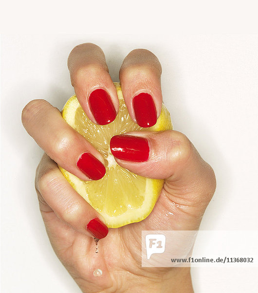 Hand of woman with red nail polish squeezing lemon