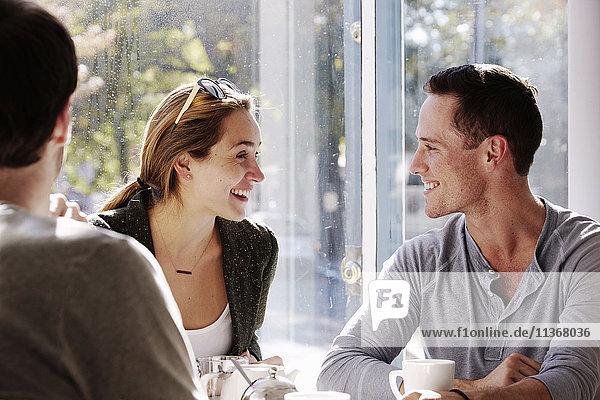 Drei Personen sitzen an einem Tisch und unterhalten sich  mit Bechern und Gläsern mit Smoothies.