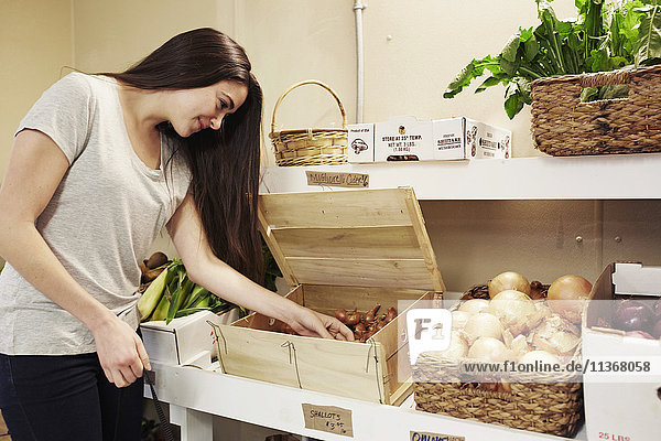 A woman choosing vegetables from a display at a farm shop.