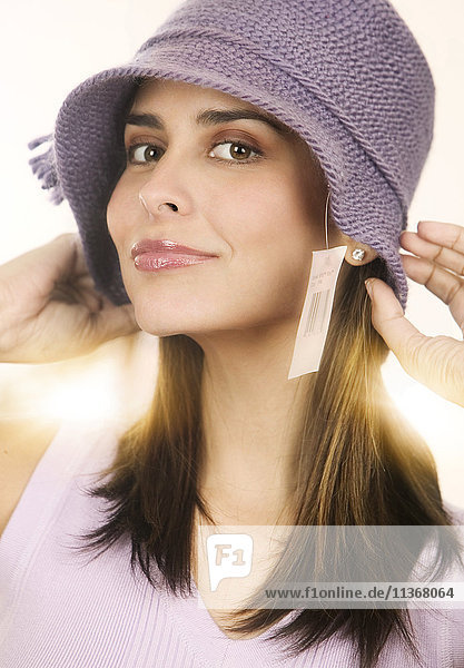 Portrait of mid adult woman trying on knitted hat