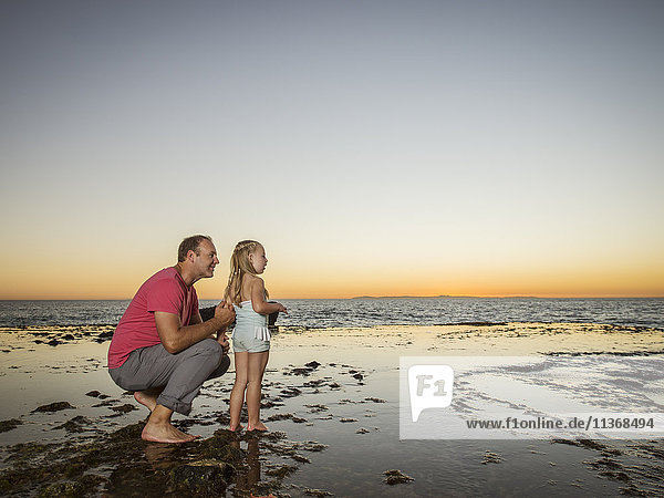 Father crouching next to daughter (4-5) on beach