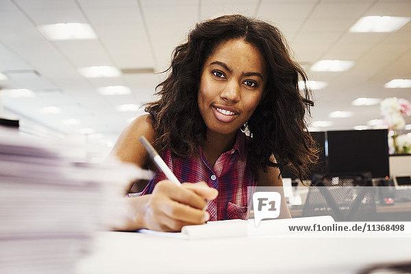 Eine Frau sitzt an einem Schreibtisch in einem Büro  hält einen Stift in der Hand und schaut in den Schuss.