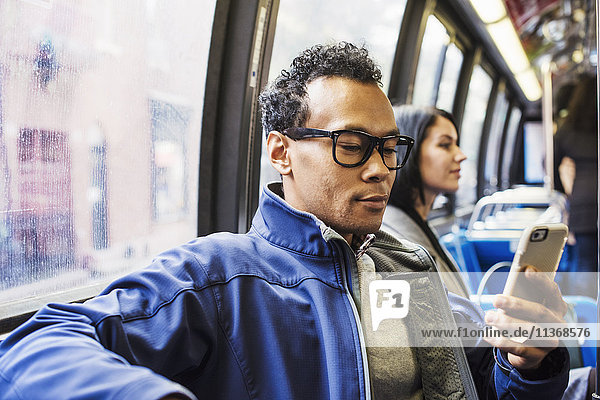 A young man and a young woman sitting on public transport looking at their cellphones.